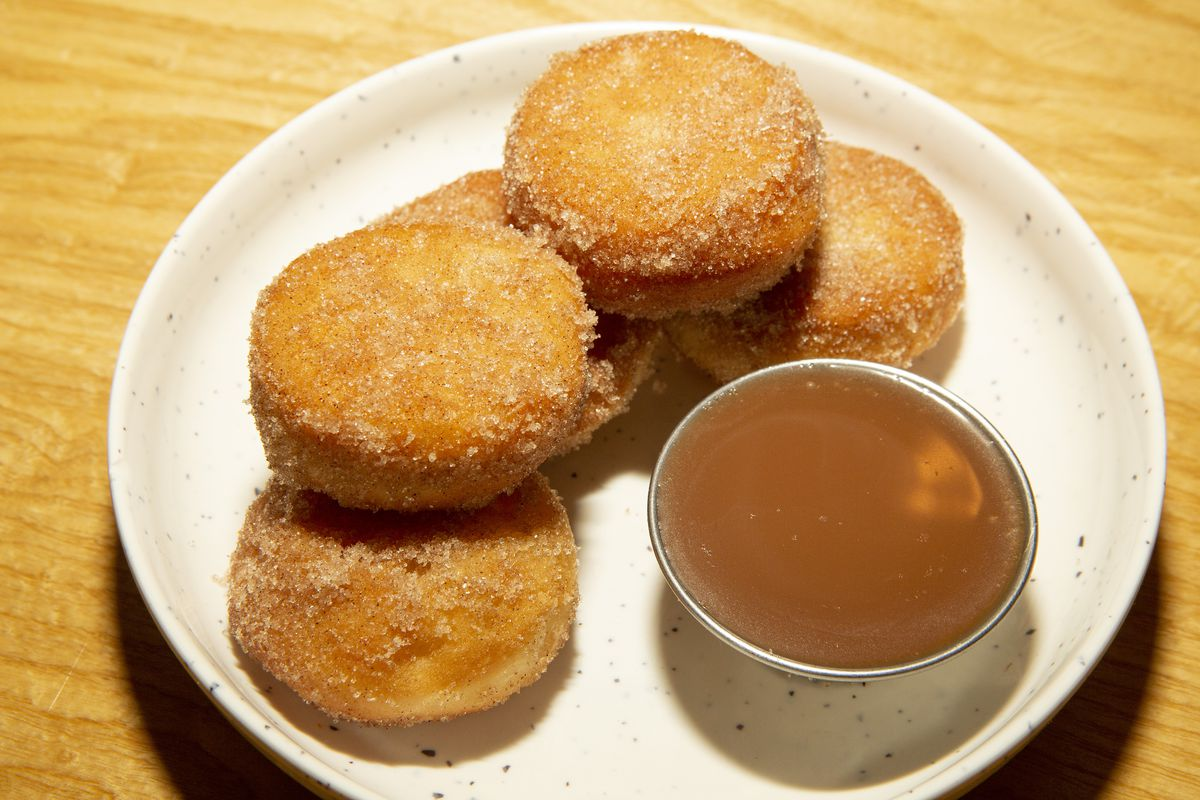 Five round donuts covered in cinnamon sugar stacked on a white plate