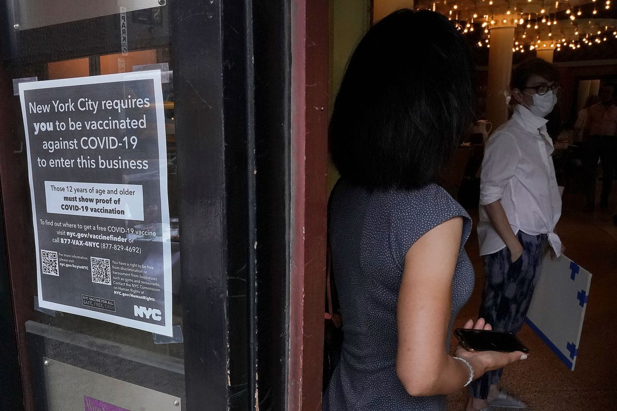 A woman waits to go in a restaurant in New York CIty, where you have to show proof of having a Covid-19 vaccination to participate in indoor dining.