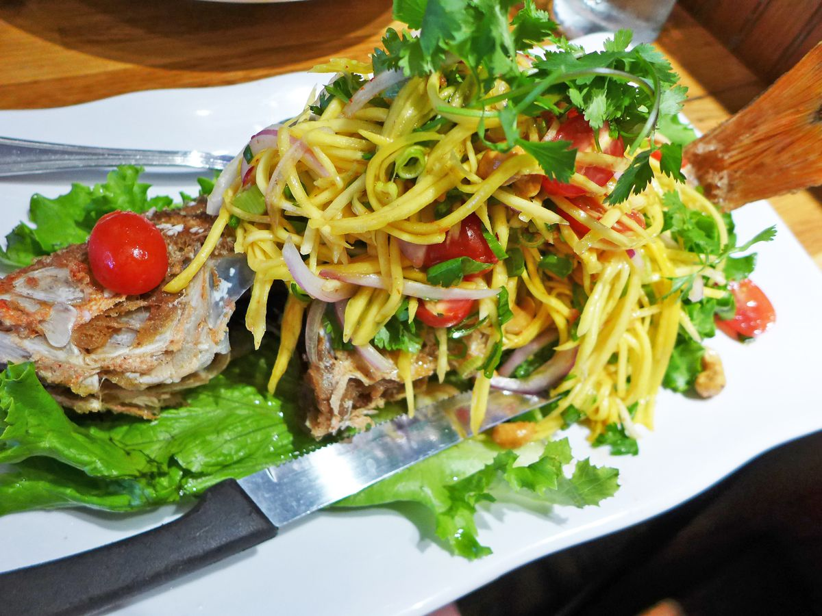 A whole fish topped with papaya salad
