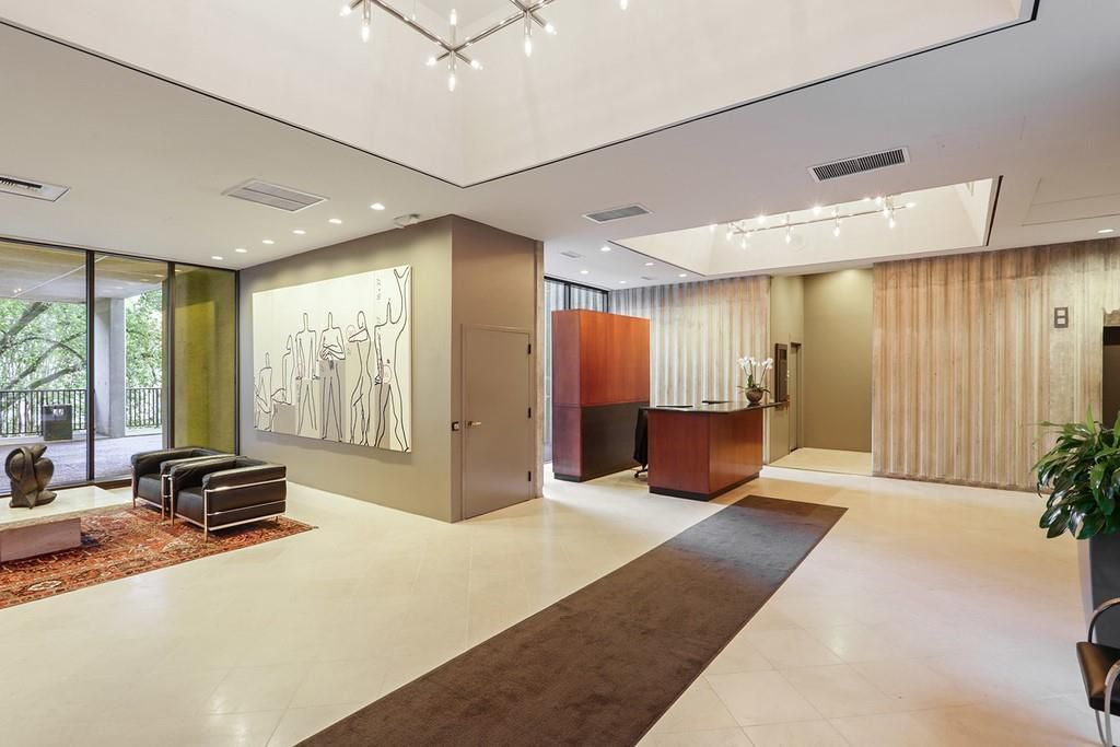 A 1970s lobby with a white ceiling and old desk.