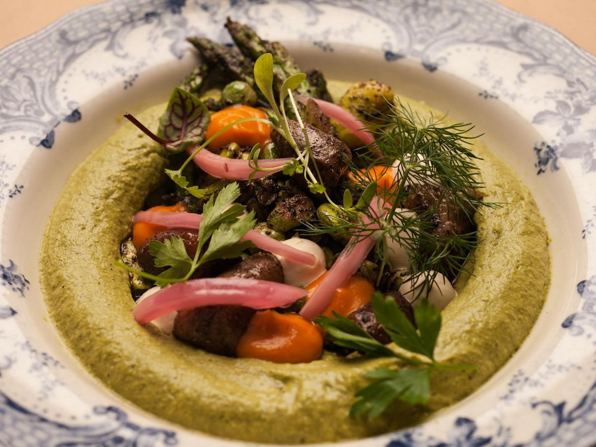 A decorative bowl filled with hummus topped with a heaping mound of vegetables, meat, and herbs