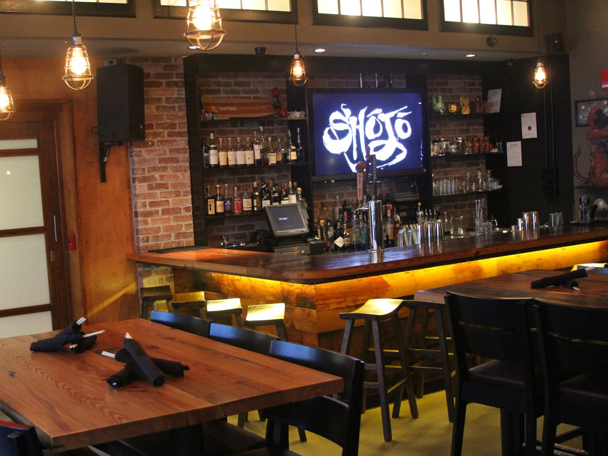 """Interior restaurant photo shows some high-top seating and a wooden bar. A television screen at the bar reads """"<span data-author=""""-1"""">Shōj</span>ō."""""""