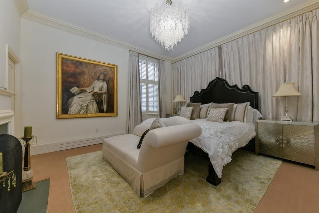 A bedroom with a bed and a couch at the end, and there's a large painting of a woman on the wall.