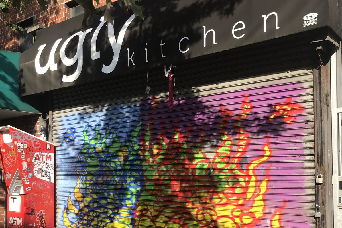 The exterior of a restaurant with a black awning and white lettering reading Ugly Kitchen. The front gate is pulled down with colorful graffiti in view on the gate. There is a red ATM to the left of the gate.
