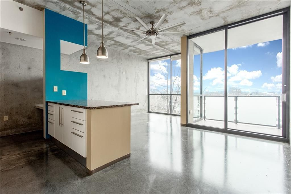 Empty living area with kitchen counters to the left and floor-to-ceiling windows in the back.
