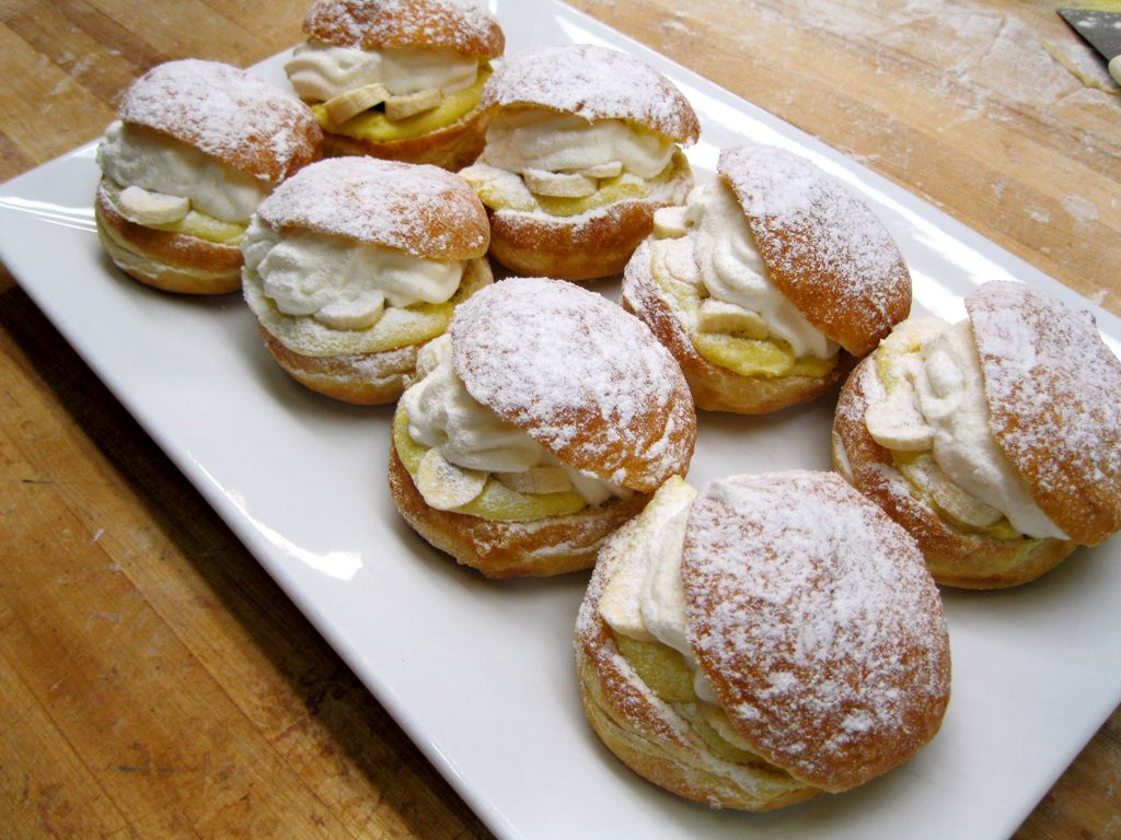 Eight filled doughnuts covered in powdered sugar on a white plate