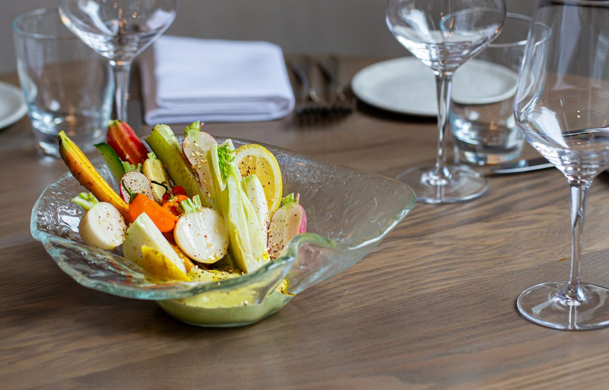 A glass bowl on a table filled with carrots and radishes crudite