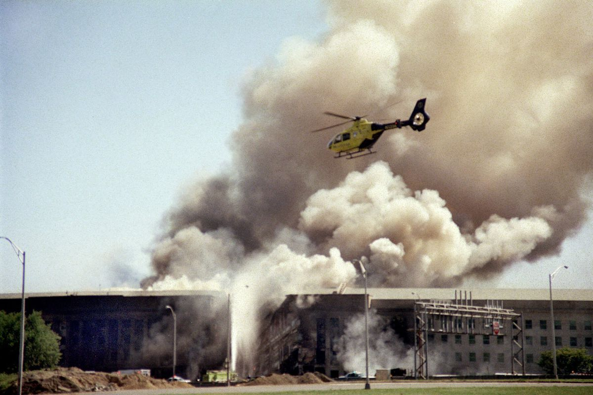 A helicopter flies over the Pentagon in Washington, Tuesday, Sept. 11, 2001 as smoke billows over the building. The Pentagon took a direct, devastating hit from an aircraft and the enduring symbols of American power were evacuated as an apparent terrorist attack quickly spread fear and chaos in the nation's capital.
