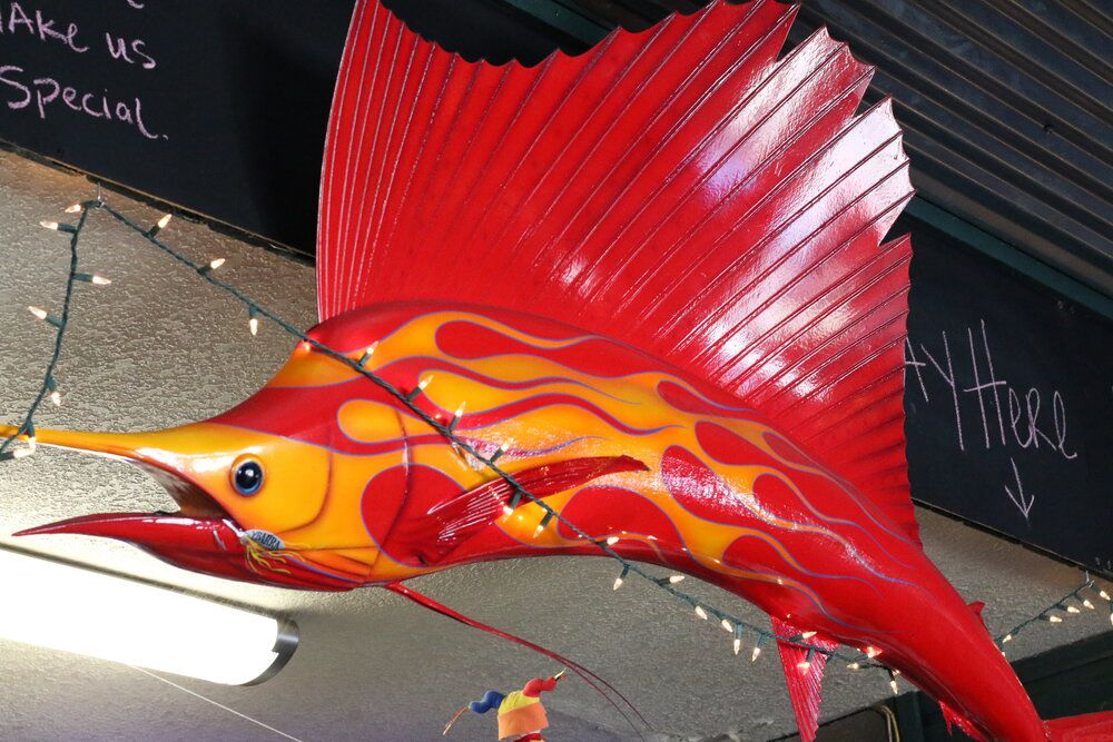 A large sailfish statue with racing flames hangs at Sage Port Grille.