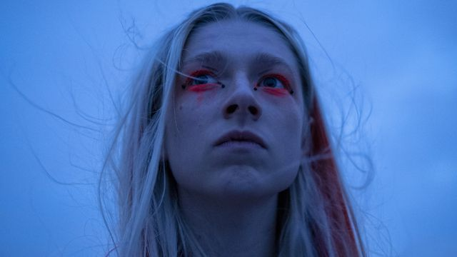 on Euphoria, a young girl with blonde hair with a red streak in it looks slightly upwards. Her eye makeup is dramatic — bright red eye shadow thickly surrounds her eyes. The background is a gray sky — she looks pensive.