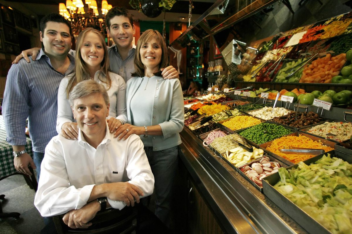 Richard Melman (front) in 2006, next to the salad bar — believed to be the first in the continental United States — in his first restaurant, R.J. Grunts. The Lincoln Park institution marks its 50th birthday Thursday. Behind him is his family, (from left): R.J., Molly, Jerrod, and Martha, his wife.