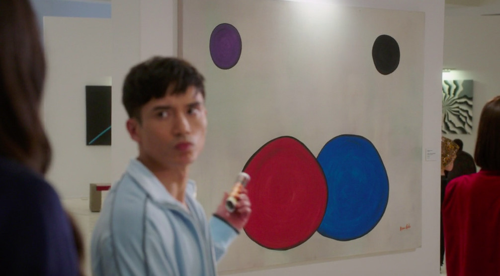 Jason pointing at a painting with red and blue circles, with smaller purple and black ones off to the side