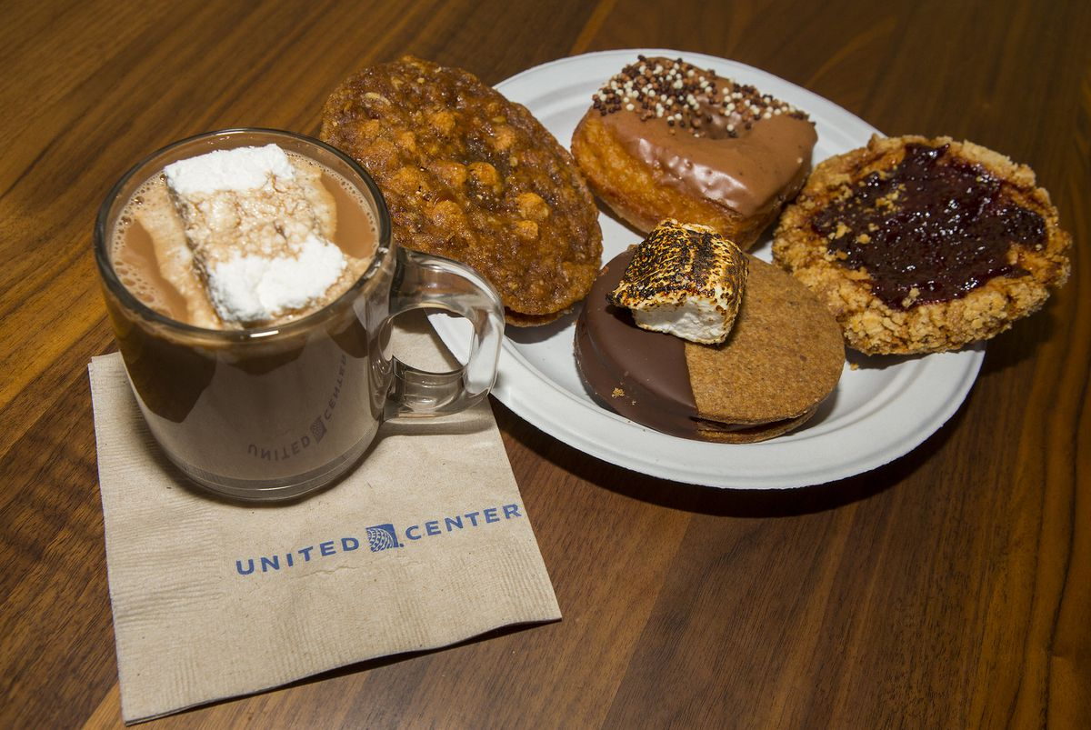 A cup of hot chocolate in a glass mug and four pastries on a paper plate.