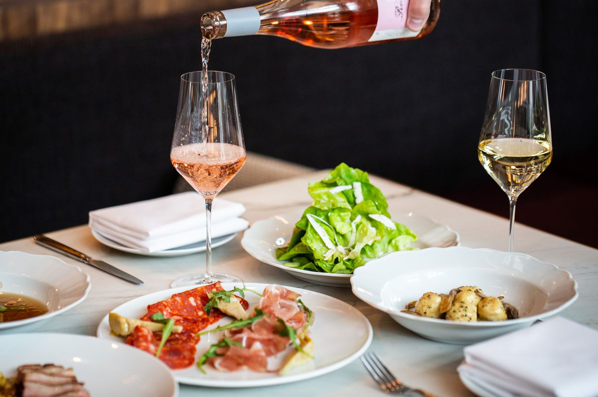A table for four includes salad, sausages and gnudi with a glass of white wine and a glass of rose, which are poured from a bottle at Lucian in Atlanta