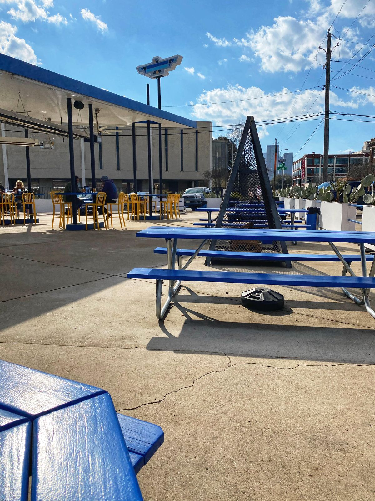 Blue picnic tables set against a backdrop of blue skies and concrete on the ground