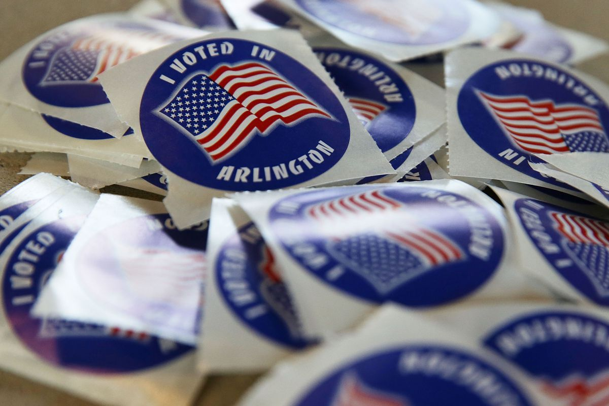 """A pile of stickers featuring an American flag and the slogan, """"I voted in Arlington."""""""