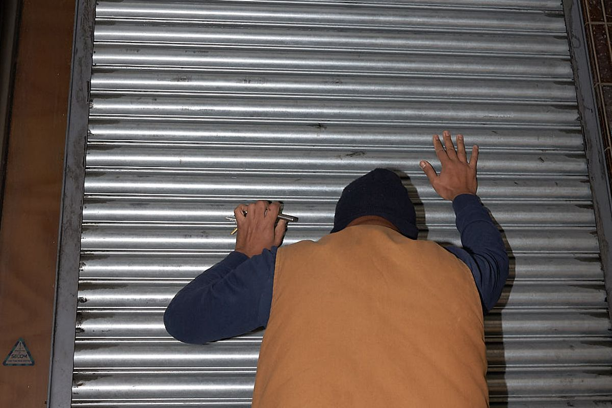 Mitshel Ibrahim pulls down the grey metal shutters at Ombra in Hackney