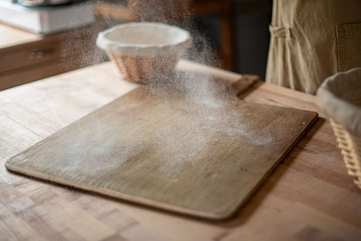 A baker drops flour lightly on a board before adding dough.
