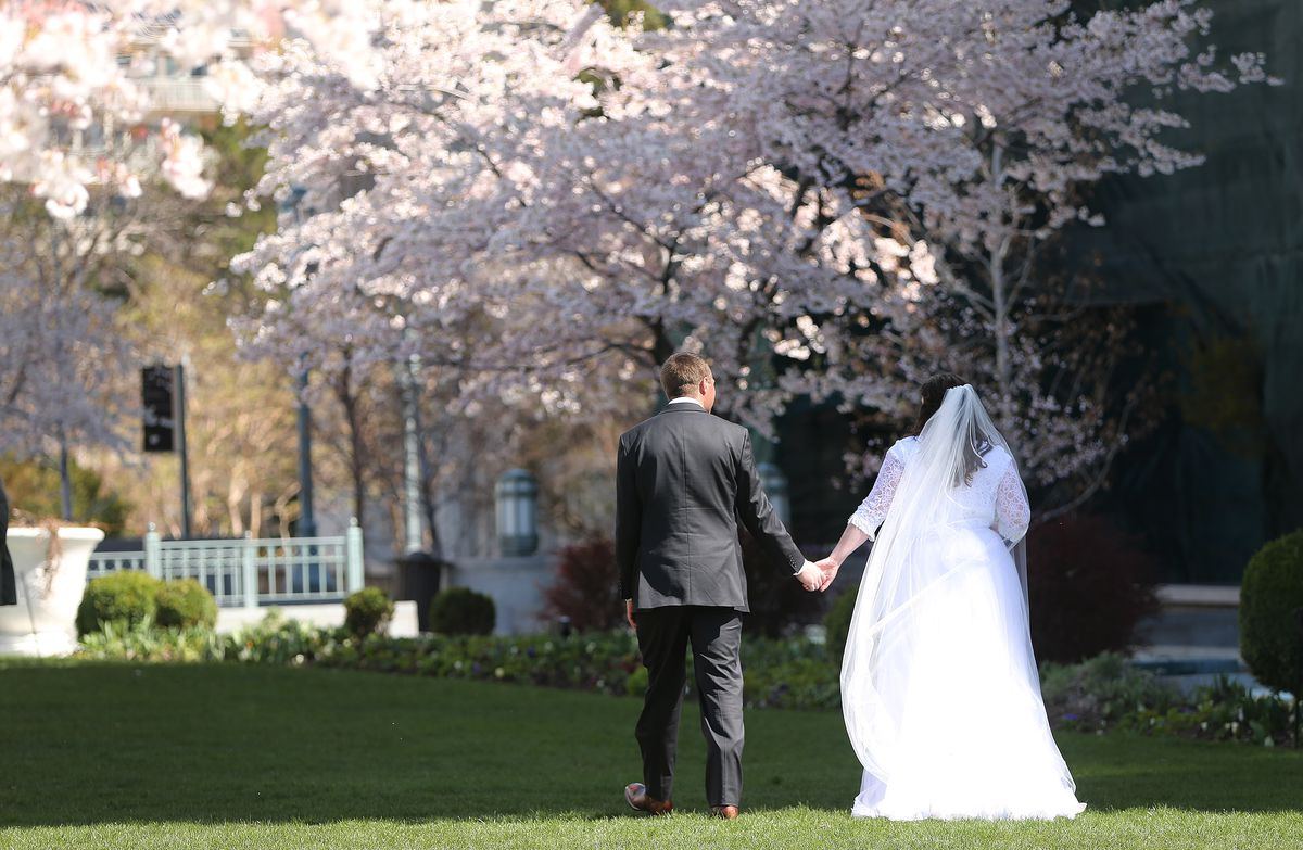 A bride and groom walk near Temple Square in Salt Lake City on Friday, April 1, 2016.