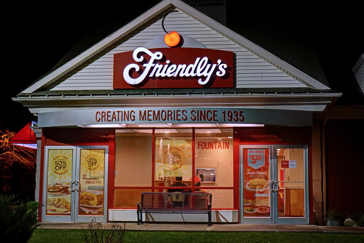 The exterior of a Friendly's restaurant, lit up inside during nighttime.