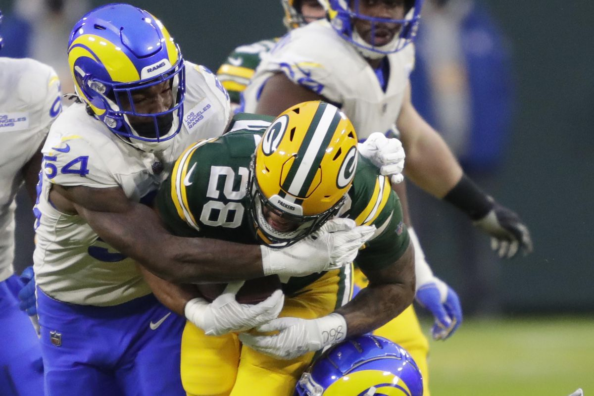 Green Bay Packers running back A.J. Dillon (28) runs for a gain against Los Angeles Rams outside linebacker Leonard Floyd (54) and safety Nick Scott (33) during their NFL divisional playoff game Saturday, January 16, 2021, at Lambeau Field in Green Bay, Wis.