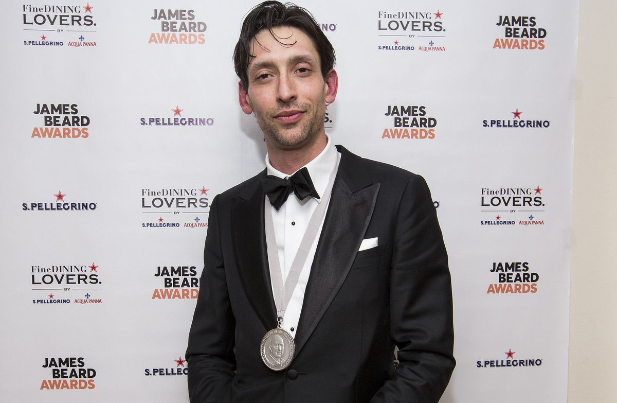 A man dressed in a back tux with a medal.