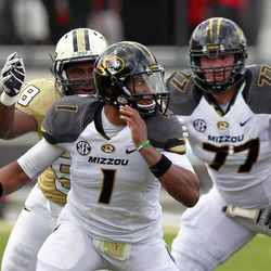 Missouri quarterback James Franklin (1) runs from the pocket away from Central Florida defensive lineman Troy Davis, left, as offensive linesman Evan Boehm (77) tries to block during the first half of an NCAA college football game, Saturday, Sept. 29, 2012, in Orlando, Fla.