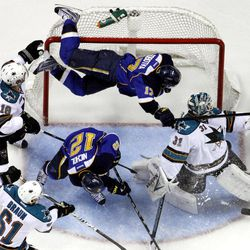St. Louis Blues' Vladimir Sobotka, top, of the Czech Republic, goes flying into the goal over San Jose Sharks goalie Antti Niemi, right, of Finland, and Blues' Scott Nichol (12) as Sharks' Dominic Moore (18) and Justin Braun (61) watch during the second period in Game 2 of an NHL Stanley Cup first-round hockey playoff series Saturday, April 14, 2012, in St. Louis.