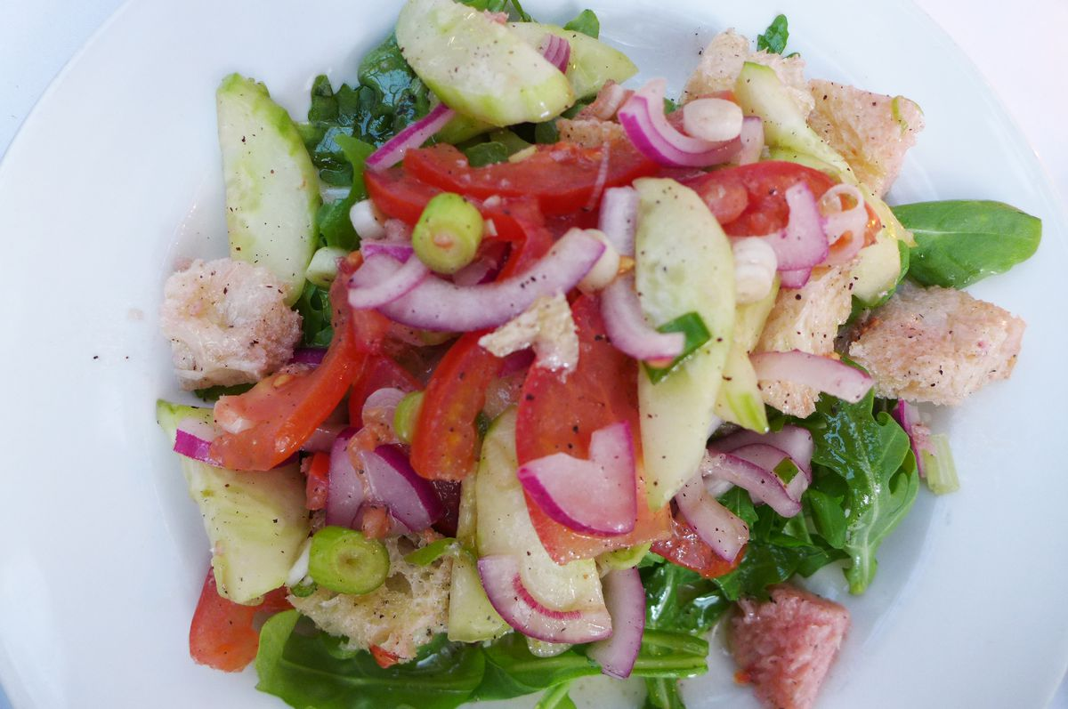 A bread salad with cucumbers, purple onions, and tomatoes.