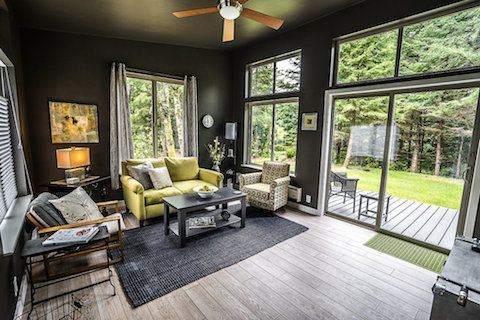 A living area with couches, arm chairs, tables, a grey area rug, and a hardwood floor. There are floor to ceiling windows overlooking a yard with trees.