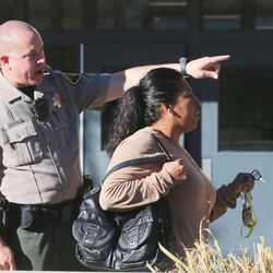 An officer directs a parent where to go to pick up a student at Mountain View High School in Orem after five students were stabbed in an apparent attack by a 16-year-old boy on Tuesday, Nov. 15, 2016.