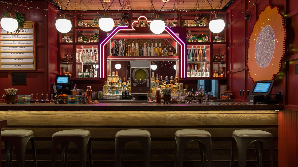 A bar with mirrors with pink neon.