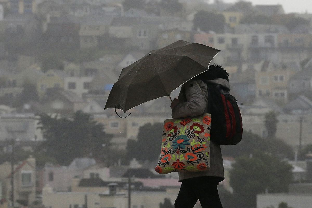 A woman carries an umbrella as she crosses a street in San Francisco, Tuesday, Feb. 7, 2017. Flash flood watches are in place for parts of Northern California down through the Central Coast as heavy rains swamp roads and threaten to overtop rivers and cre