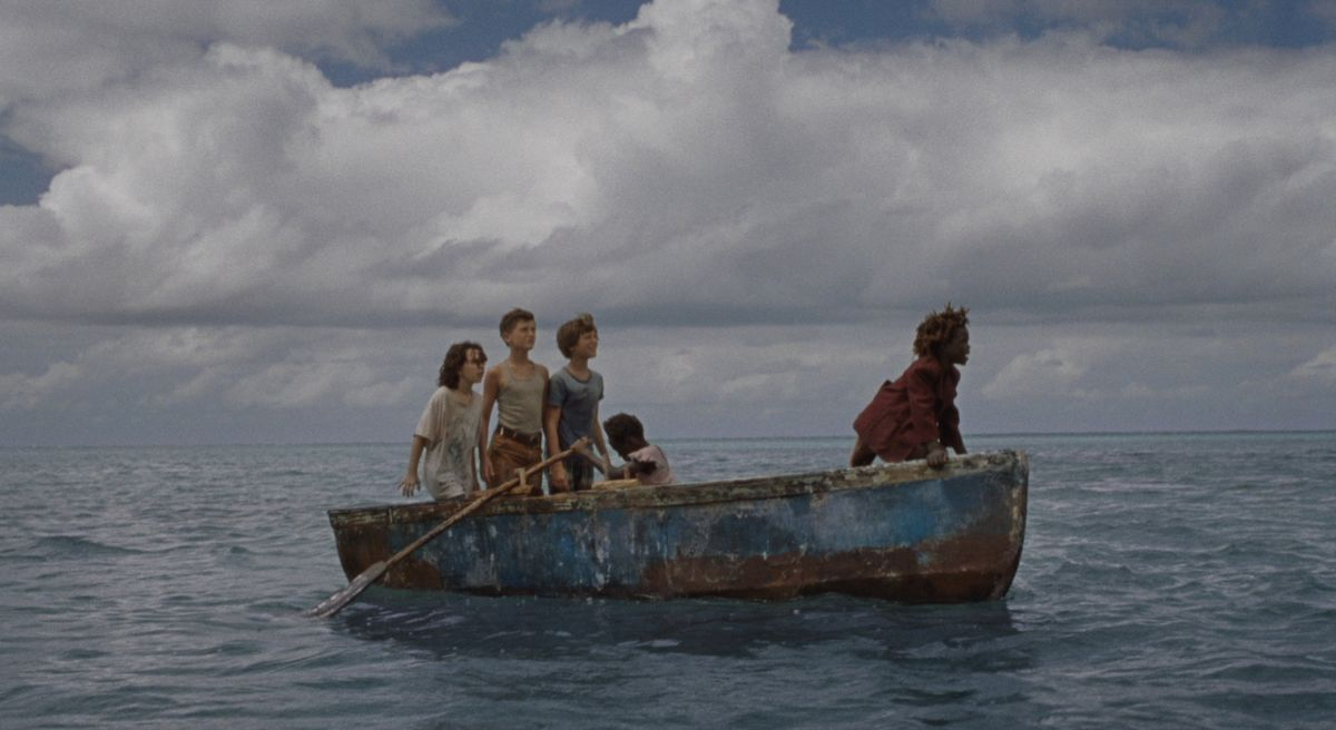 Five kids sail on the ocean in a battered, rusty blue dinghy, with vast white clouds overhead.
