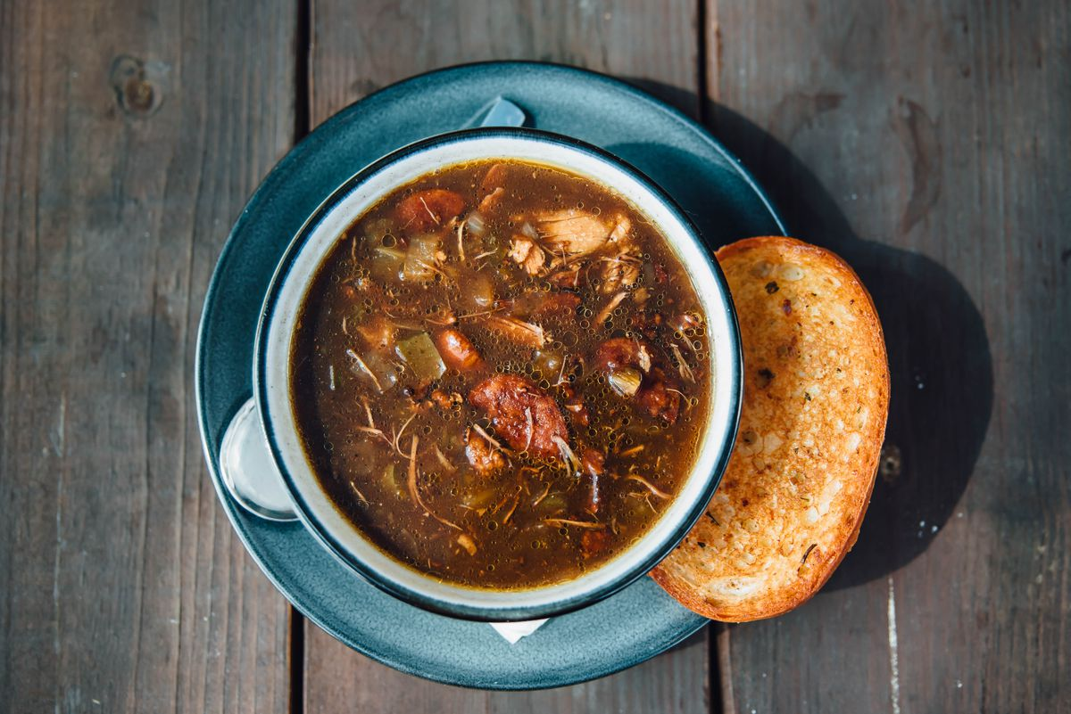 Duck and andouille gumbo in a white bowl on top of a teal blue plate with a slice of toast next to it. All sits on a wood table,
