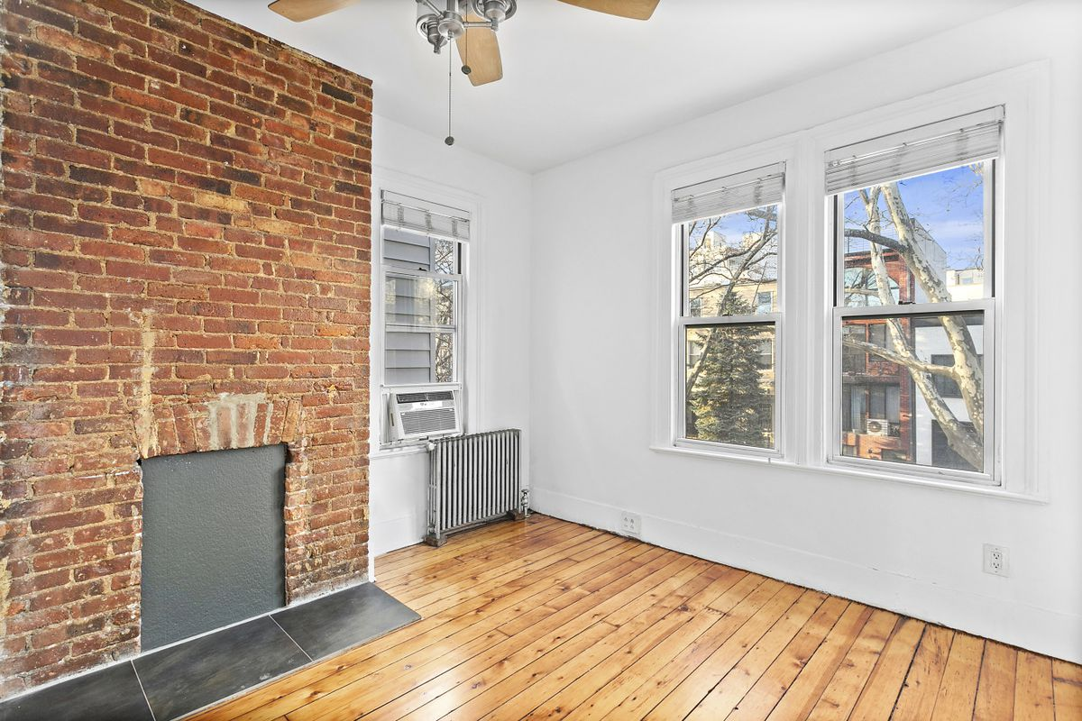 A living room with a ceiling fan, hardwood floors, exposed brick, and three windows.