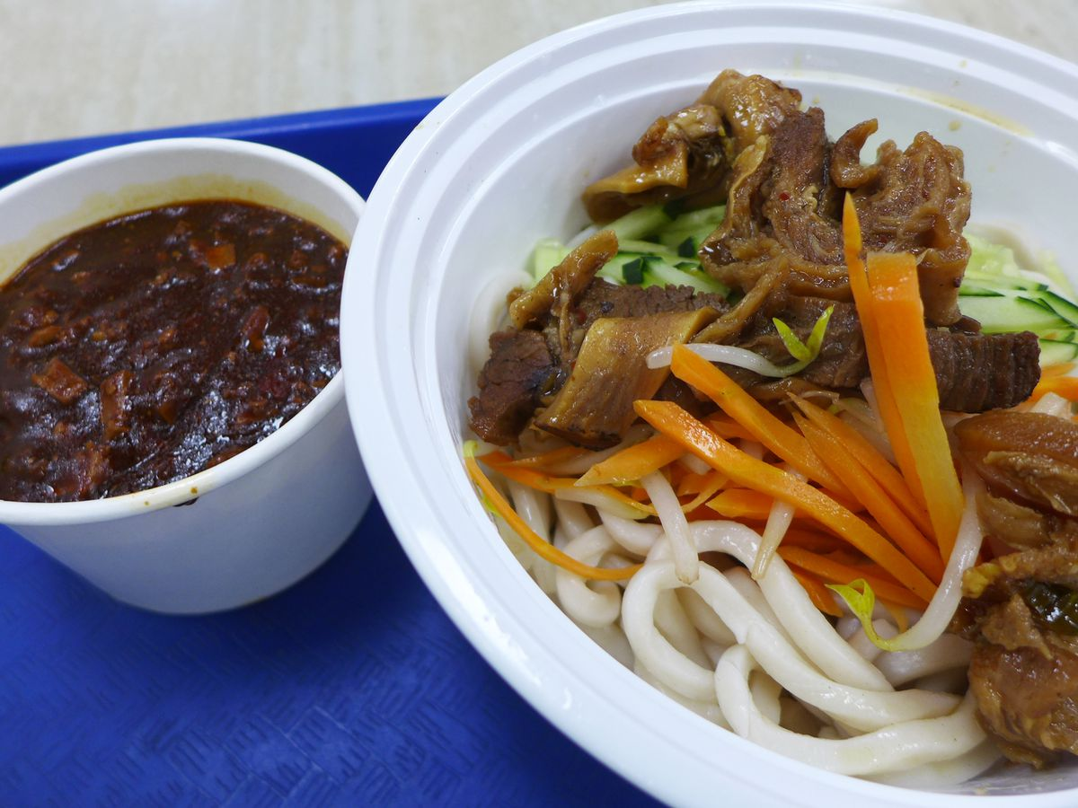 A white plastic bowl with shredded carrots, hunks of bony beef, and fat white noodles, with a dark bowl of been paste on the side.