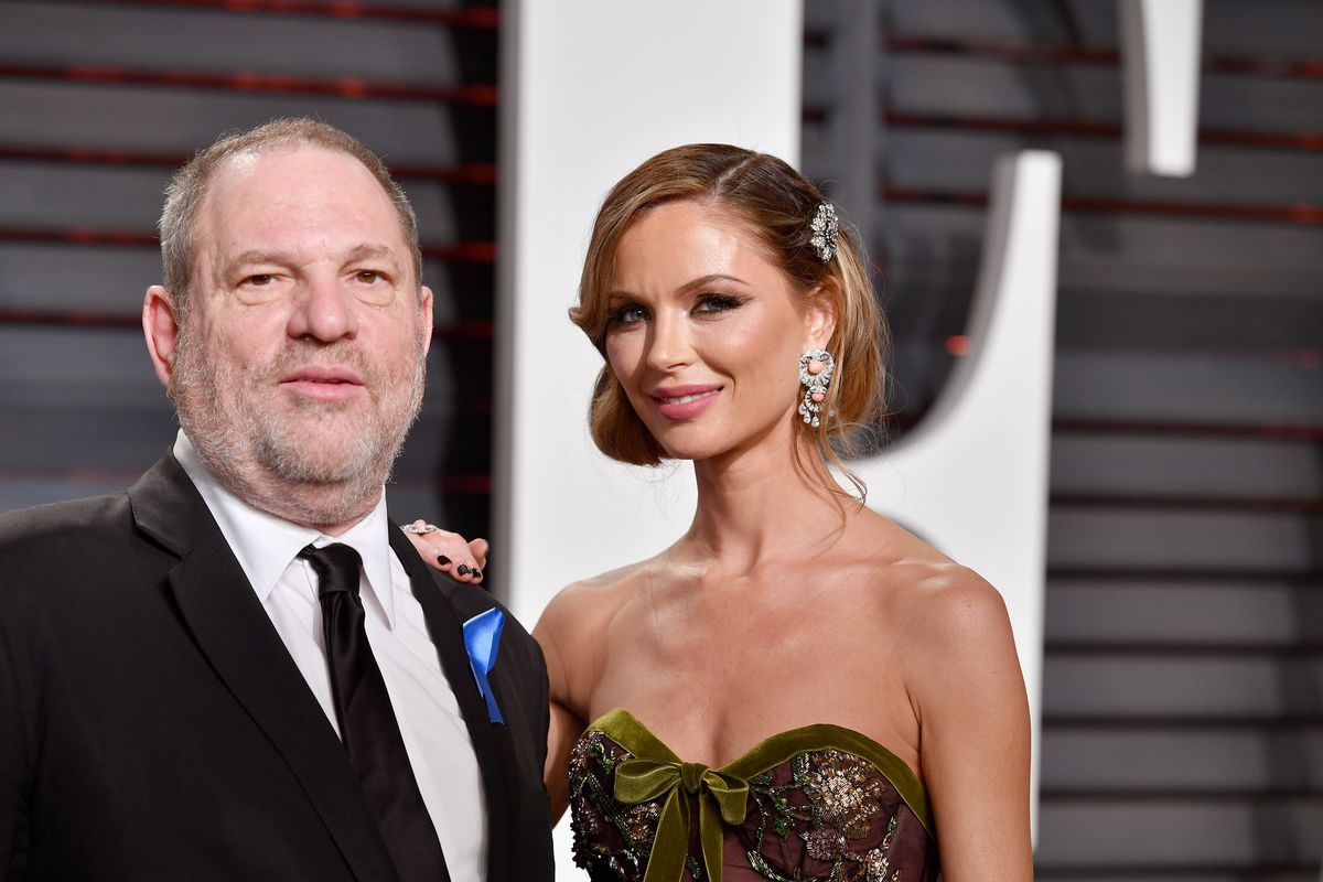 """Weinstein and Chapman pose together in front of a big """"VF"""" sign."""