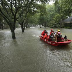 A Coast Guard rescue team evacuates people from a neighborhood inundated by floodwaters from Tropical Storm Harvey on Monday, Aug. 28, 2017, in Houston, Texas.
