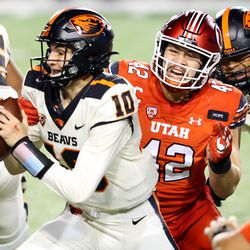 Utah Utes defensive end Mika Tafua (42) brings down Oregon State Beavers quarterback Chance Nolan (10) as Utah and Oregon State play a college football game at Rice Eccles stadium in Salt Lake City on Sunday, Dec. 6, 2020. Utah won 30-24.