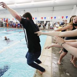Lone Peak swimmers throw their coaches Calvin Smith and Celeste Tiffany into the pool as they celebrate their team win in the 6A girls swim championship at Kearns Oquirrh Park Fitness Center in Kearns on Saturday, Feb. 20, 2021.