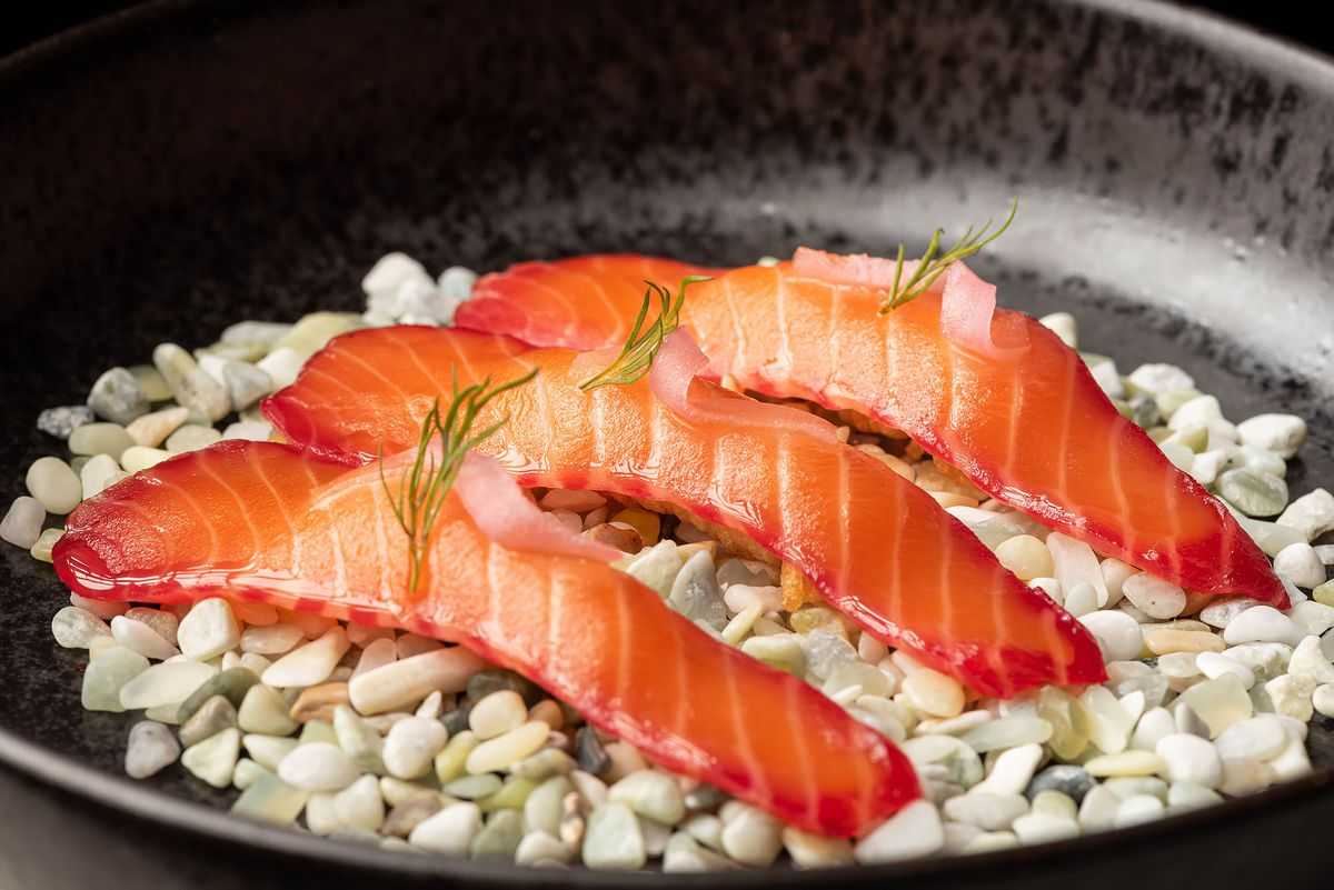 Aged king ora salmon over small pebbles on a plate.