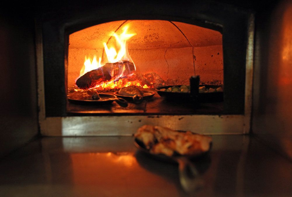 Food cooking in wood-fired hearth