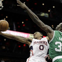Atlanta Hawks' Jeff Teague, left, puts up a shot past Boston Celtics' Brandon Bass  during the second quarter of Game 1 of an opening-round NBA basketball playoff series, Sunday, April 29, 2012, in Atlanta.