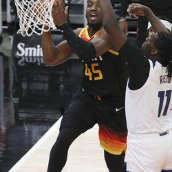 Utah Jazz guard Donovan Mitchell (45) drives on Minnesota Timberwolves center Naz Reid (11) in Salt Lake City on Saturday, Dec. 26, 2020.