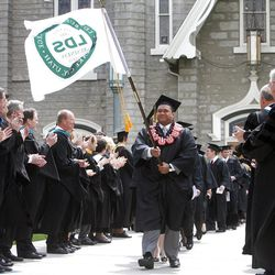 Kauulufonua Toutai carries the school's flag as students make their way into LDS Business College's commencement on Friday. LDS Business College's 125th Commencement exercise Friday, April 13, 2012.
