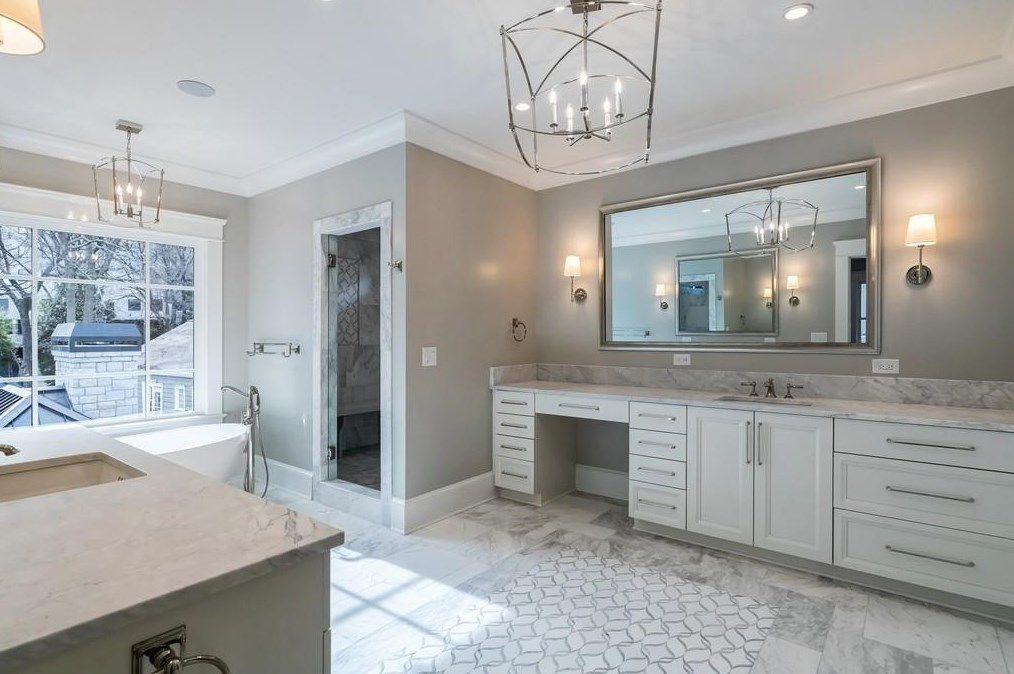 A huge white marble bathroom with a window to the city.