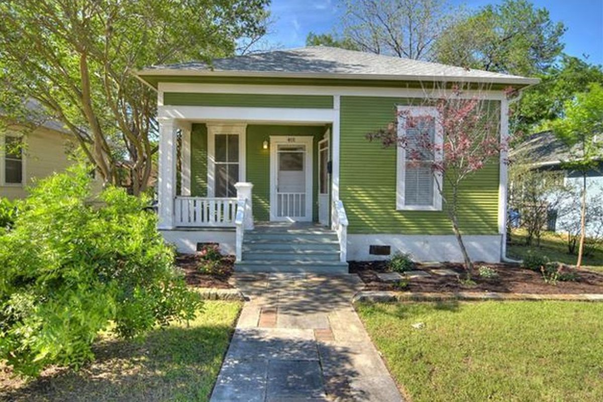 Small wooden home painted bright green with white trim