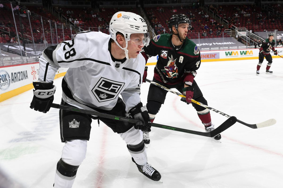 Jaret Anderson-Dolan #28 of the Los Angeles Kings looks for the puck while being defended by Niklas Hjalmarsson #4 of the Arizona Coyotes at Gila River Arena on February 18, 2021 in Glendale, Arizona.