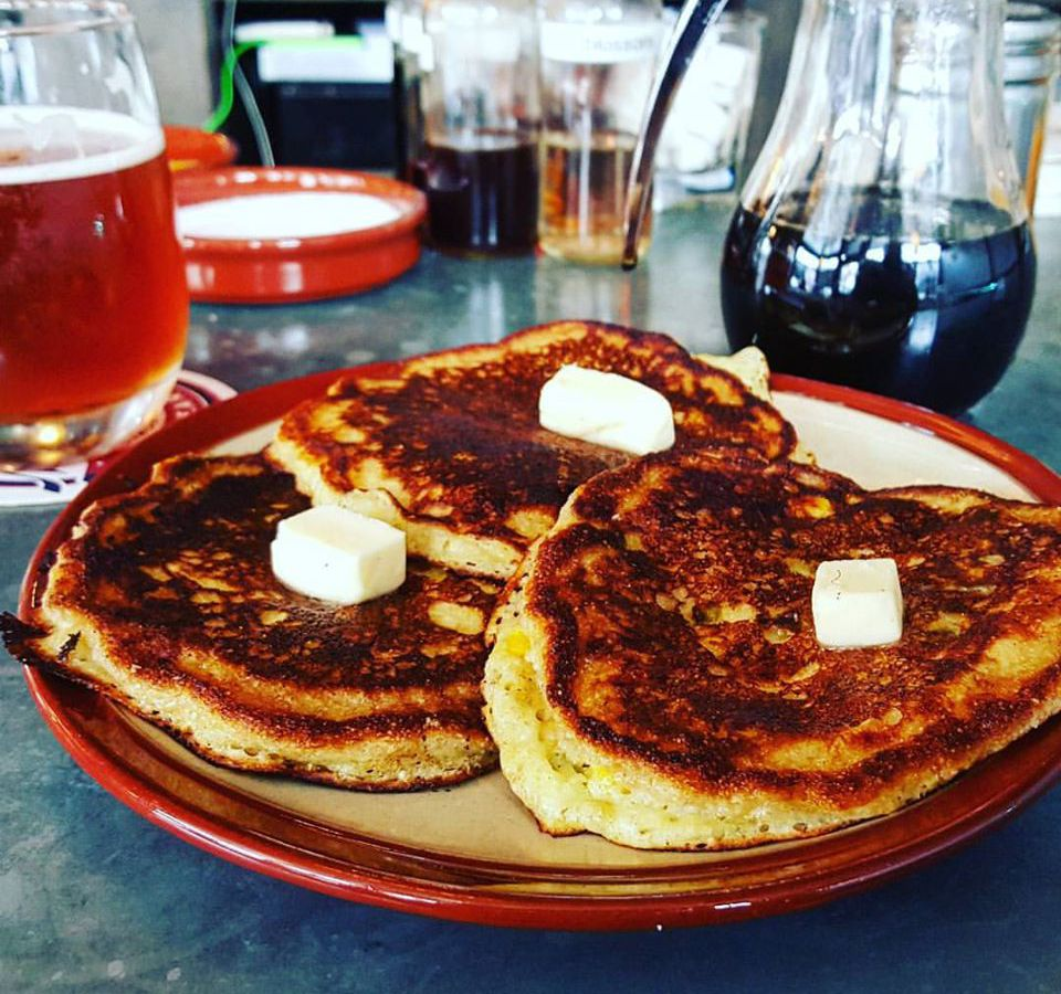 Three browned pancakes sit on a plate, each with a pat of butter on top. A beer is visible in the background.
